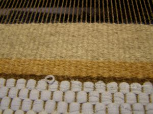 Close up of hand weaving on loom